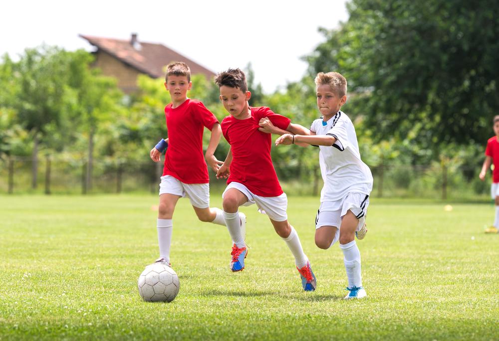 サマースクールでサッカーをする少年